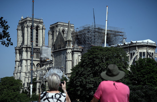 tourists looking at the damaged Notre Dame